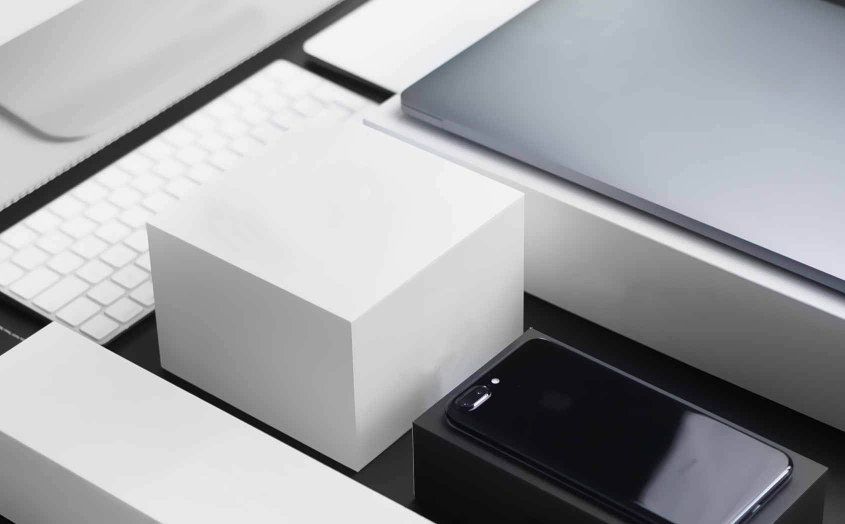Apple products spread out on a table, boxes, keyboards, phones and computers