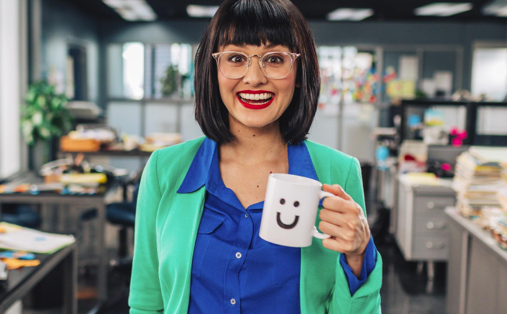 Woman in colorful clothes holding mug with Funraise smiley face in drab nonprofit office space