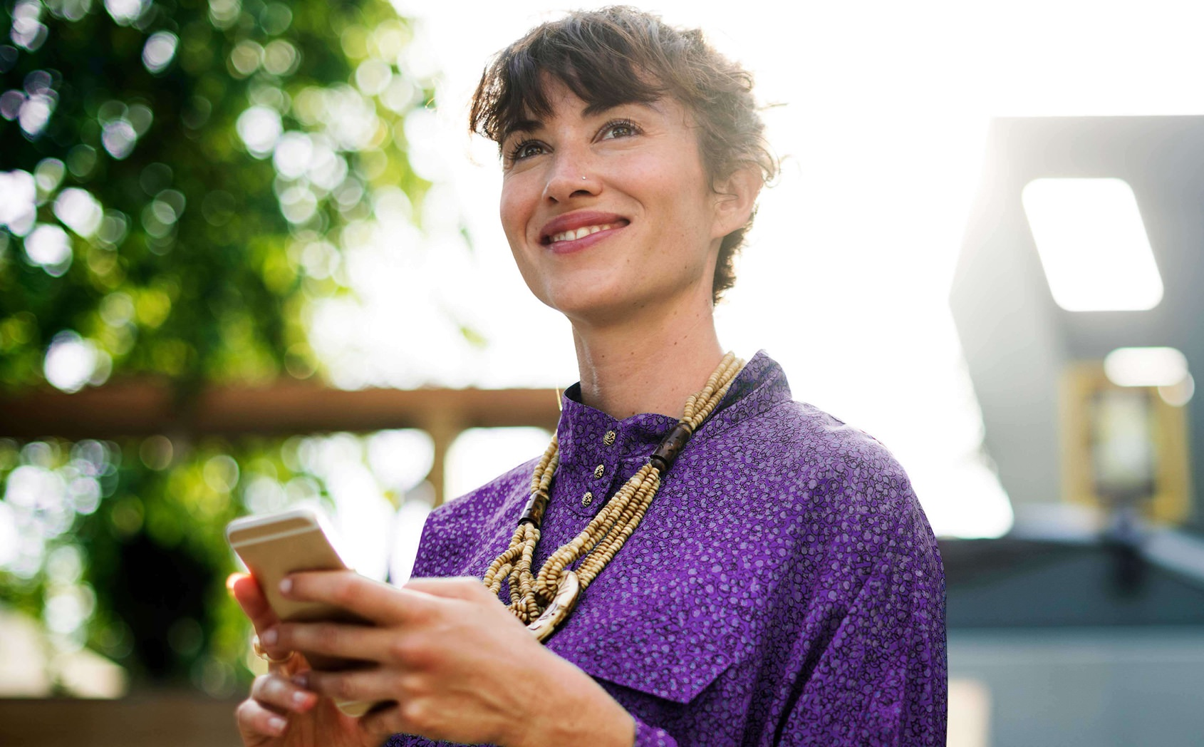 Smiling young woman holding smart phone and looking up