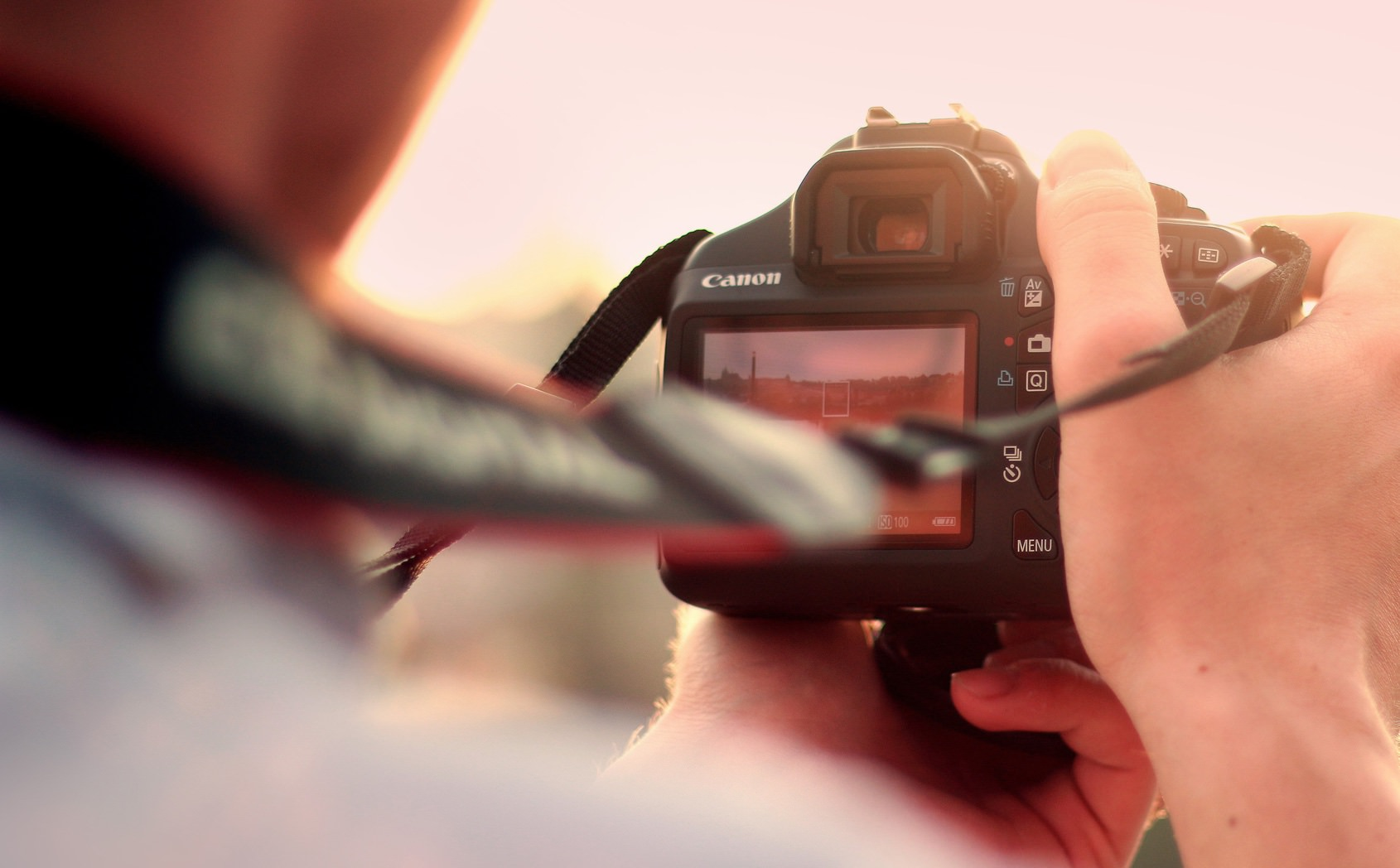 Closeup of Canon DSLR camera in photographer's hands