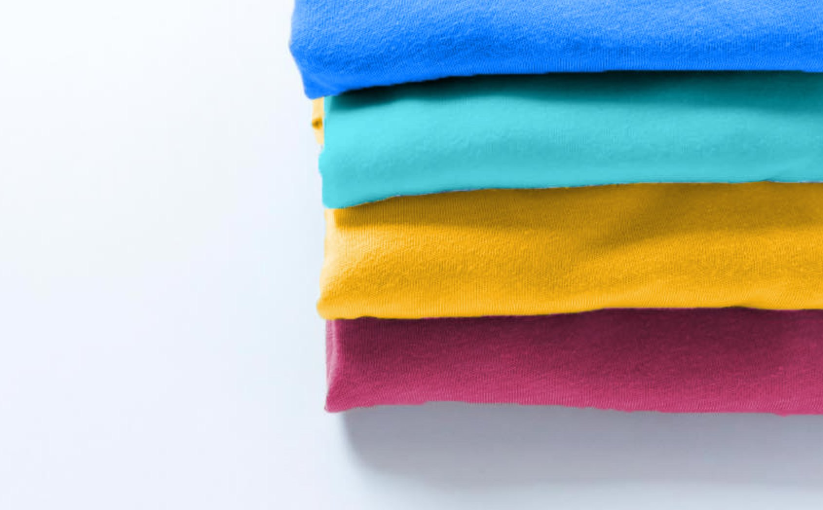 Colorful t-shirts, folded and stacked on a table
