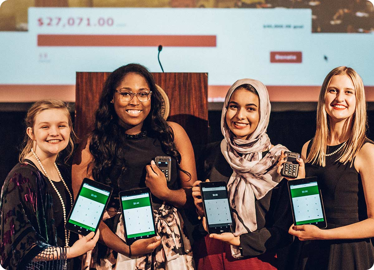 Four young smiling women stand in front of a screen displaying a fundraising progress bar that is three-quarters of the way to their goal. Each woman is holding a tablet device and a funraise reader device for accepting donations.