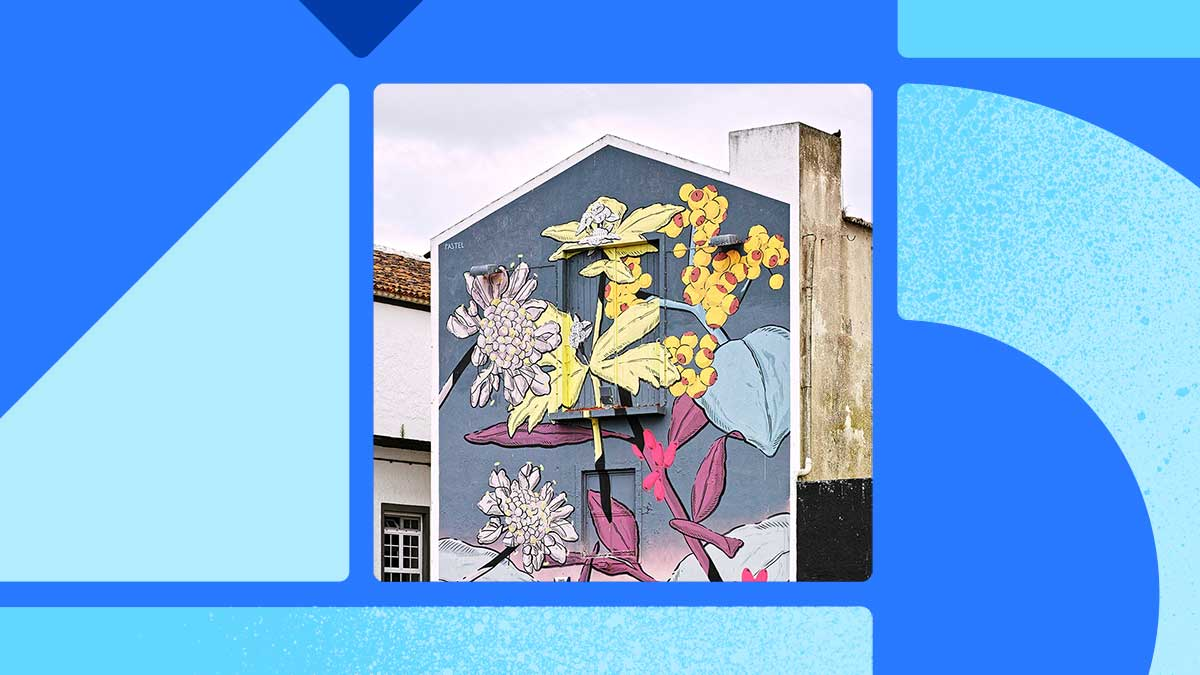 Photo of a stone building that has a huge mural on the side of it. The mural is a muted blue background with lavender, yellow, light blue, and mauve plants painted on it. The photo is in a square set on a blue background with blue shapes surrounding it.