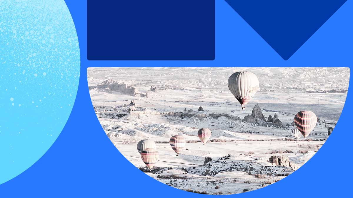 Photo of a winter wonderland landscape covered in white snow and ice. In the sky are hot air balloons floating calmly. The photo is in a half-moon shape set on a blue background with blue shapes.