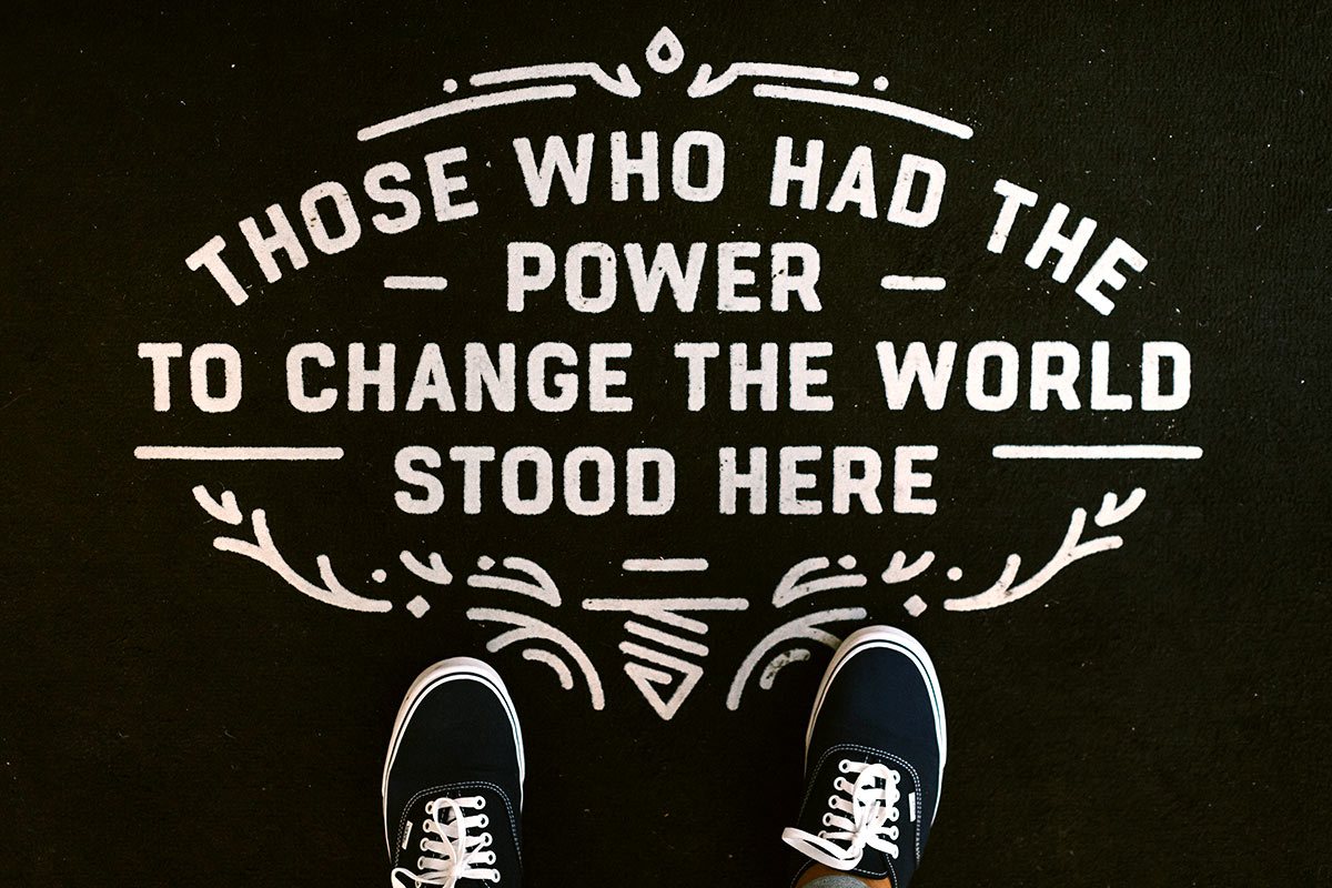 "Black background with white script lettering saying, ""Those who had the power to change the world stood here."" There are black sneakers with white laces at the bottom of the image, making it look like the picture was taken from above."