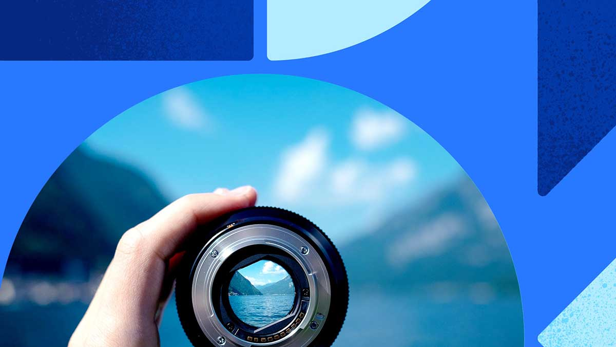 Photo of a gorgeous water vista shown through a camera lens. The lens is held in a person's hands. The photo is overlaid on a background of blue with blue shapes.