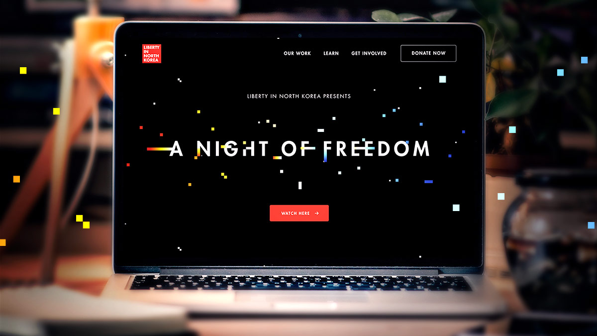 "A laptop sits on a desk in a dark room. On the screen is the Liberty In North Korea virtual gala home page. It reads ""A Night of Freedom"" with a button that says ""Watch Here""."