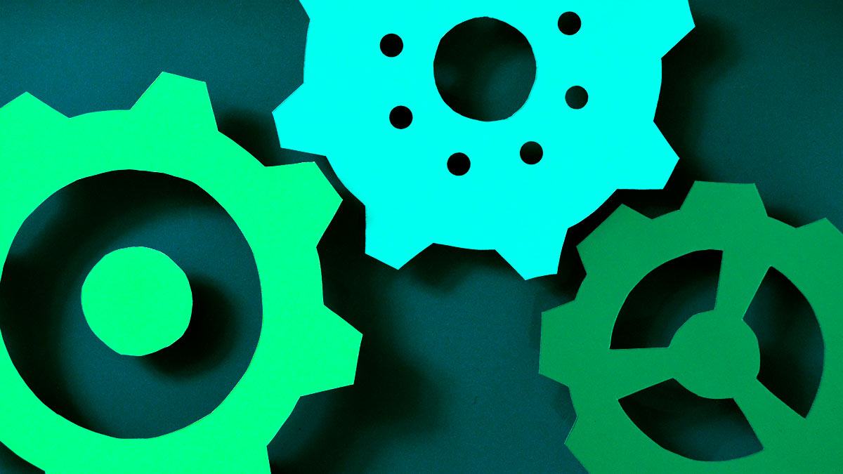 Three gears work together in unison. They're made of bright, colorful paper, and photographed from above with dark shadows behind them.