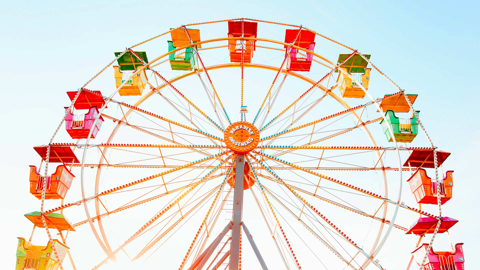A colorful Ferris wheel with the sun glowing behind it.