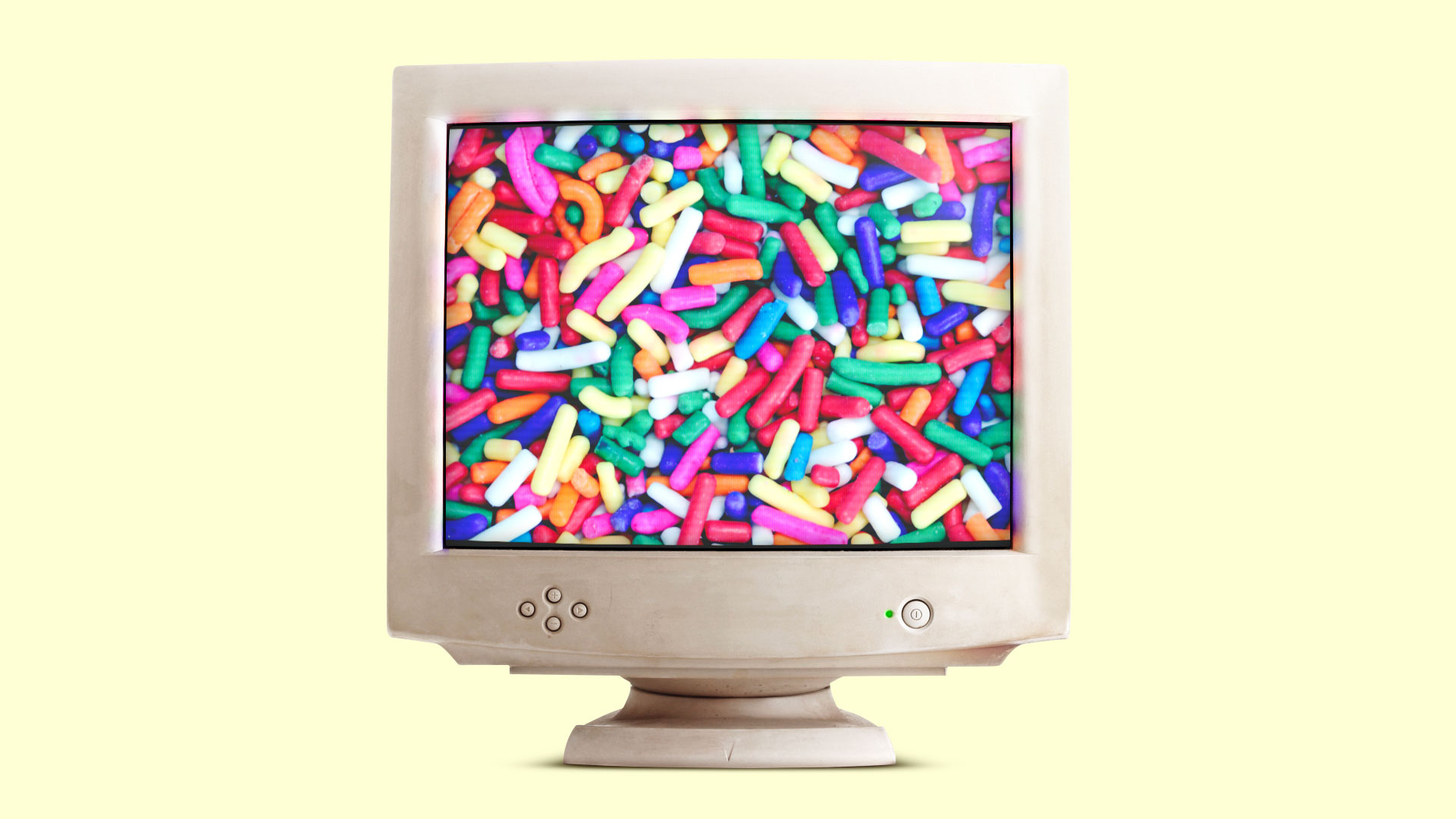 An old computer monitor displays a close-up shot of colorful candy sprinkles.
