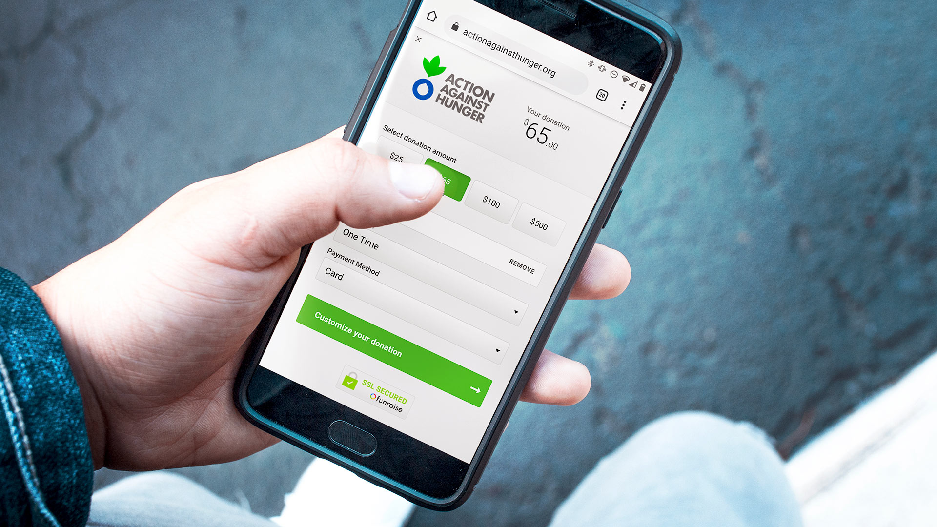 Action Against Hunger's Funraise Donation Form is displayed on a phone in someone's hand. The person is clicking on a button to donate $65, and appears to be standing outdoors, donating on the go.