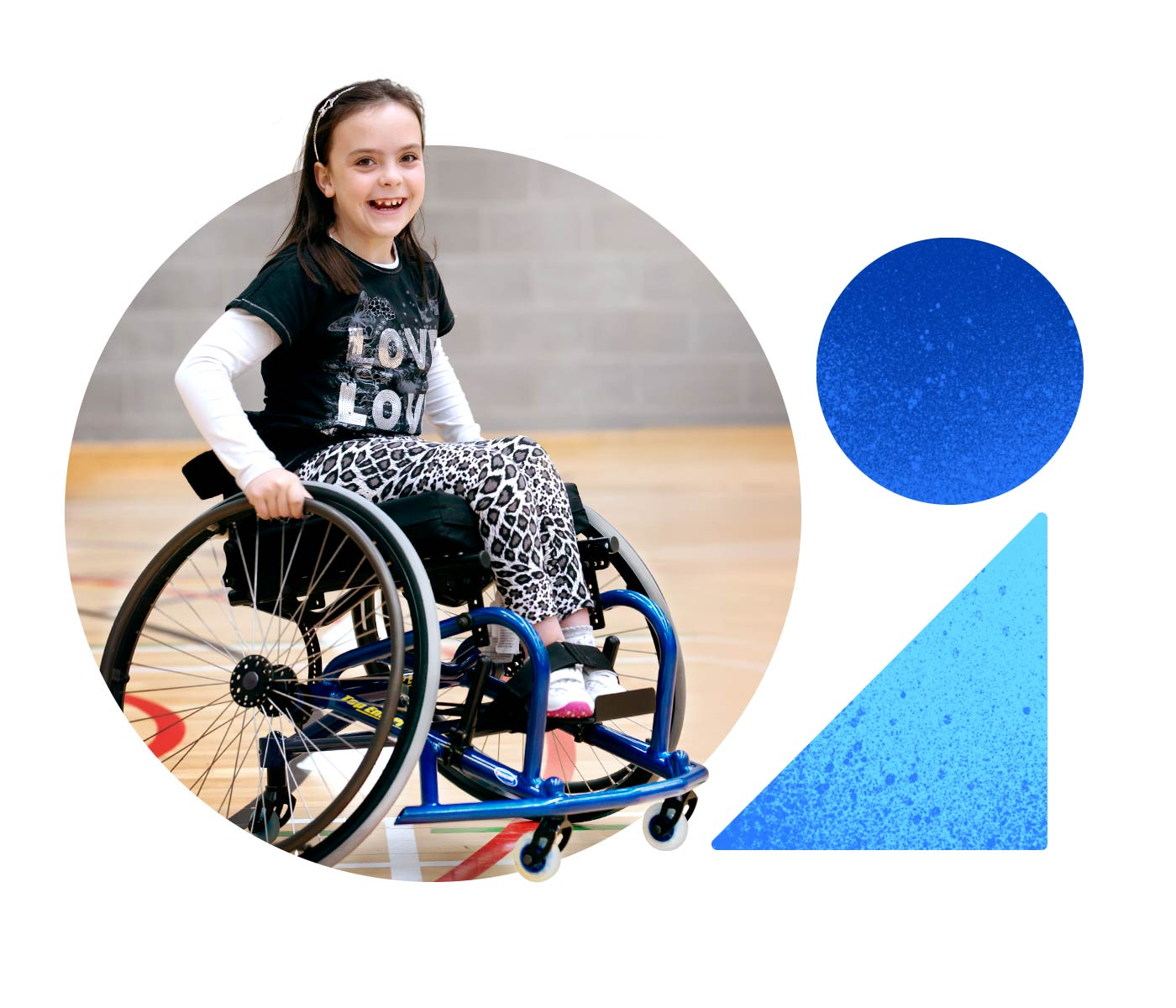 A young girl smiles as she moves her wheelchair across a basketball court