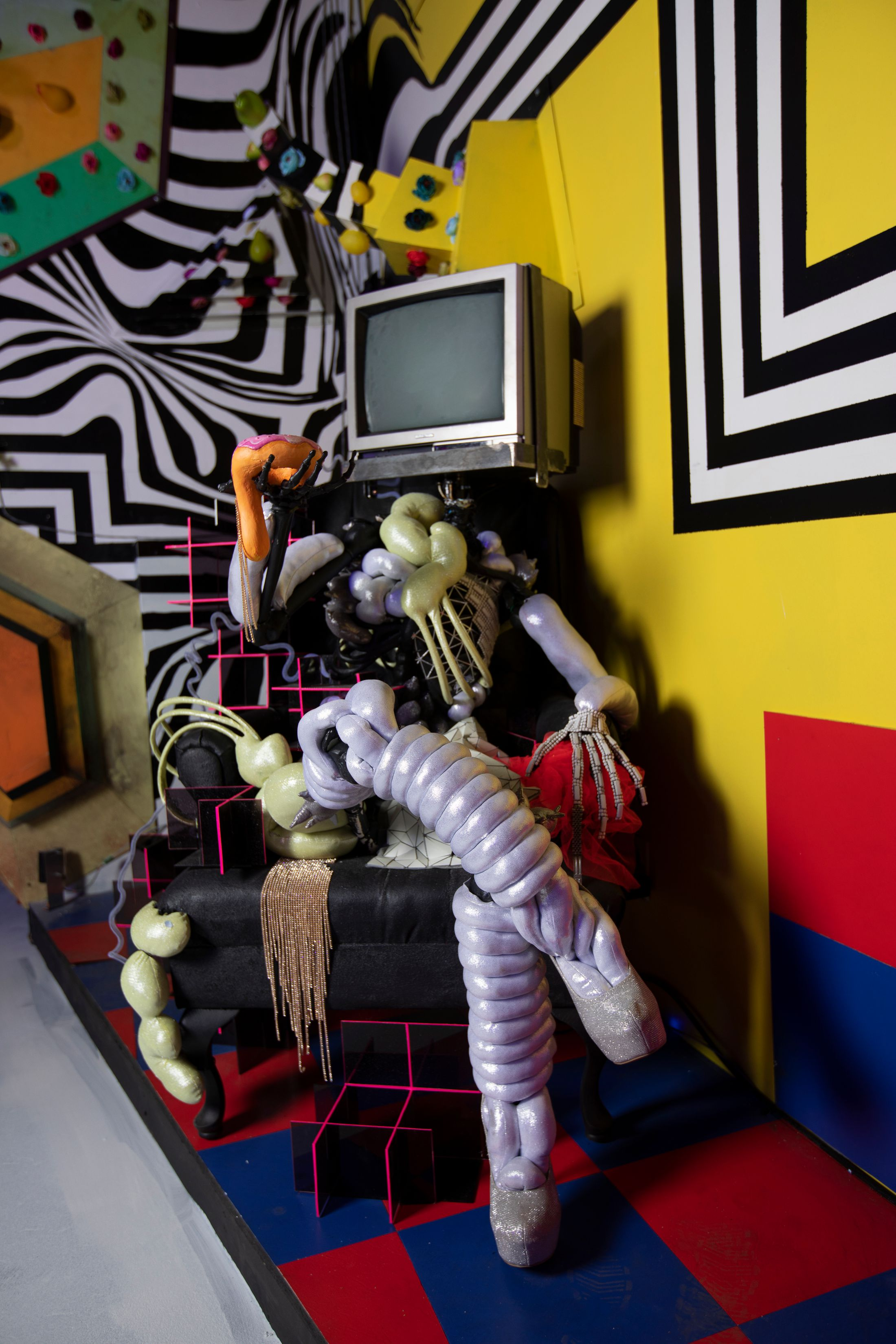 A TV being held up by various items that resemble parts of a body, with the TV in place of the head