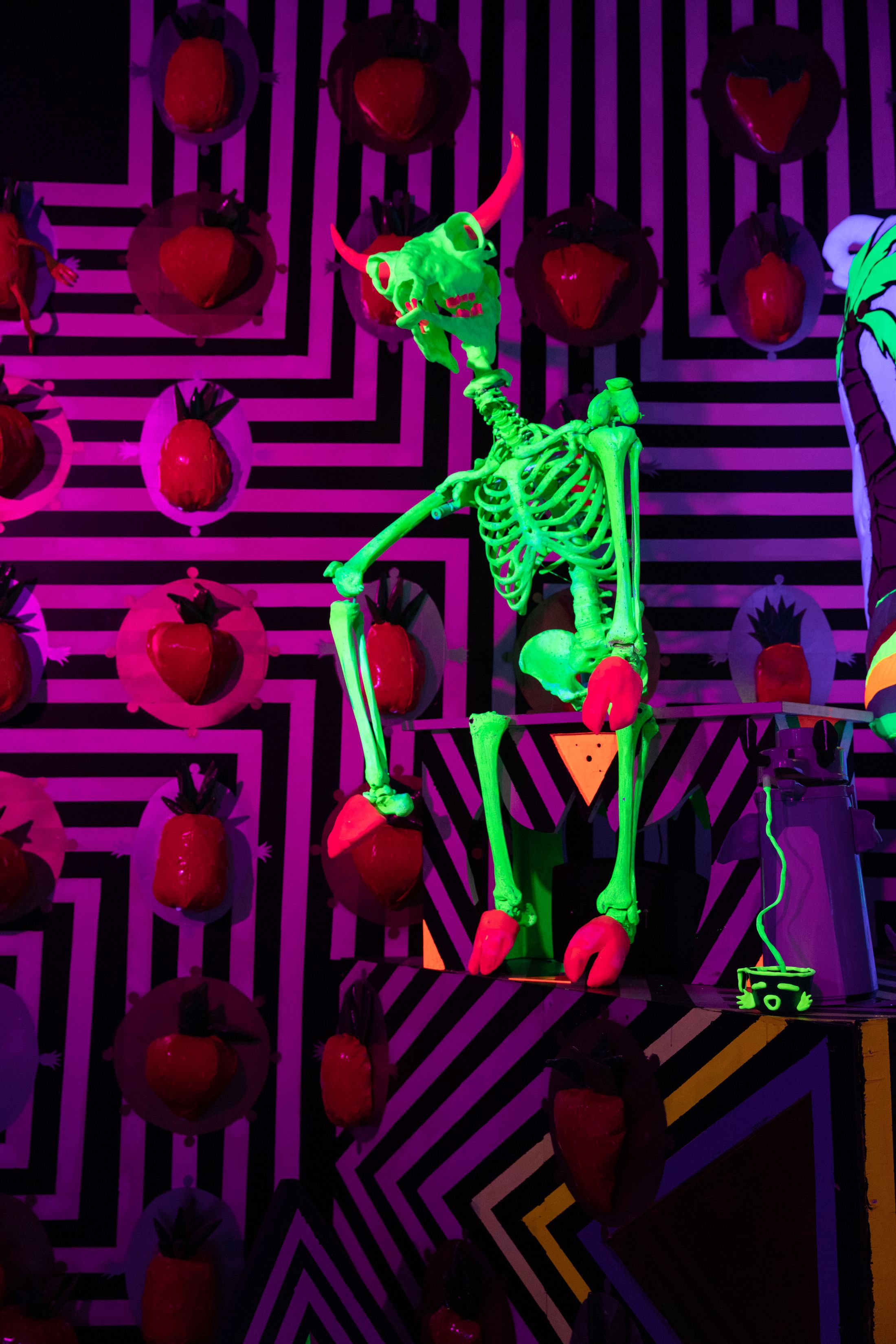 Neon skeleton against a striped wall
