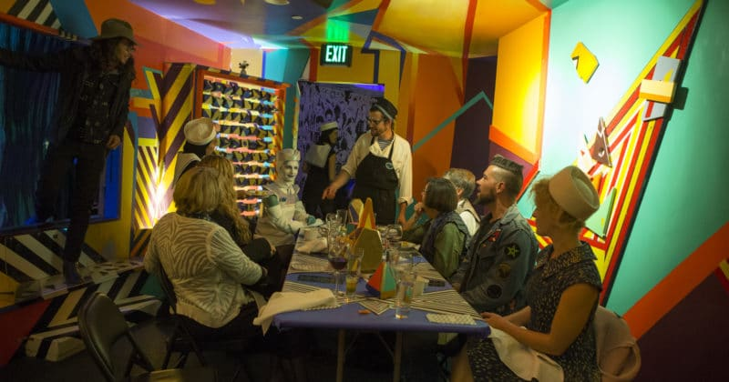 people sitting around a dinner table inside Meow Wolf Santa Fe