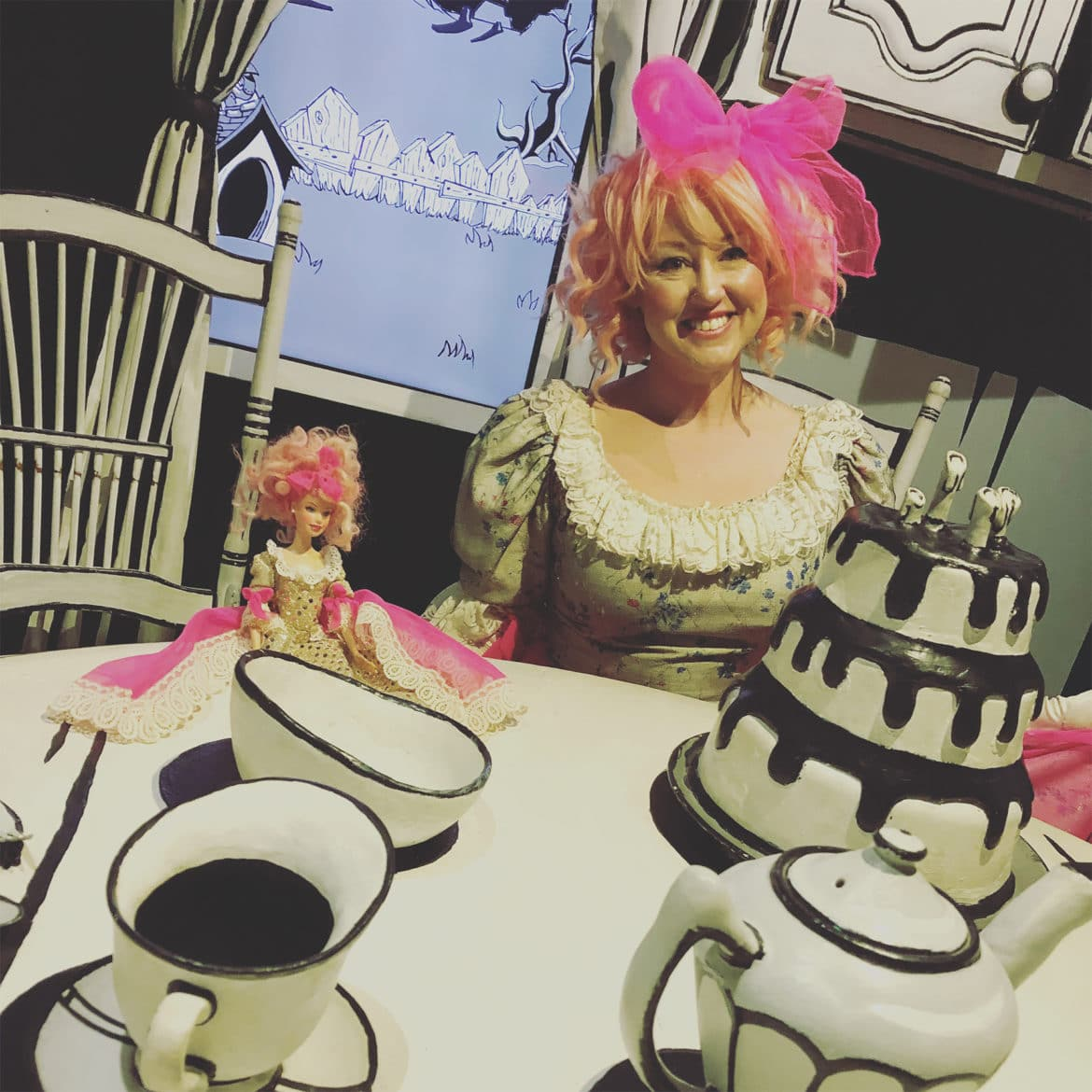 person with pink wig sitting at black and white table