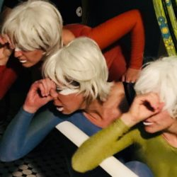 three women with white hair looking through glasses