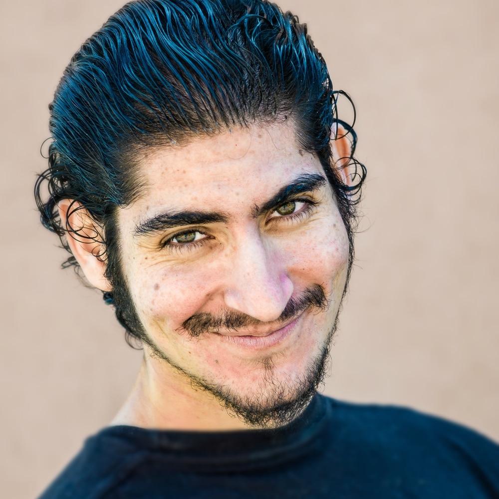Man with dark hair and facial hair looking at camera