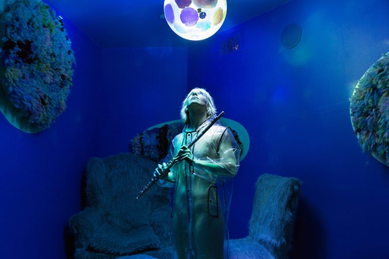 Person standing looking up at a glowing ball in a vivid blue room.