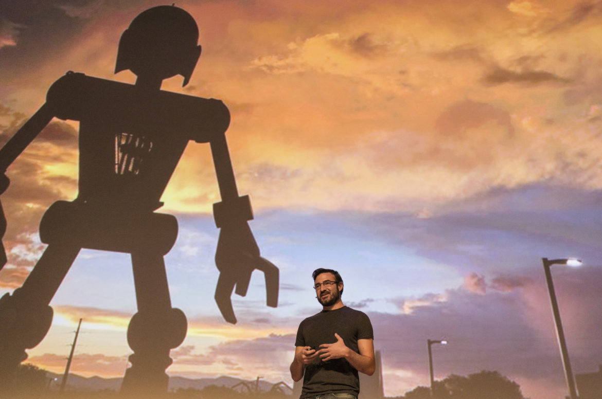 person standing under giant robot at dusk