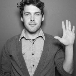 person with curly hair standing against a wall with hand up