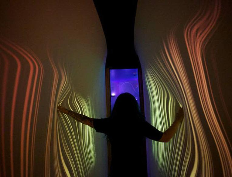 Person standing with light coming from hands on walls at art exhibit room at Meow Wolf in Santa Fe, NM