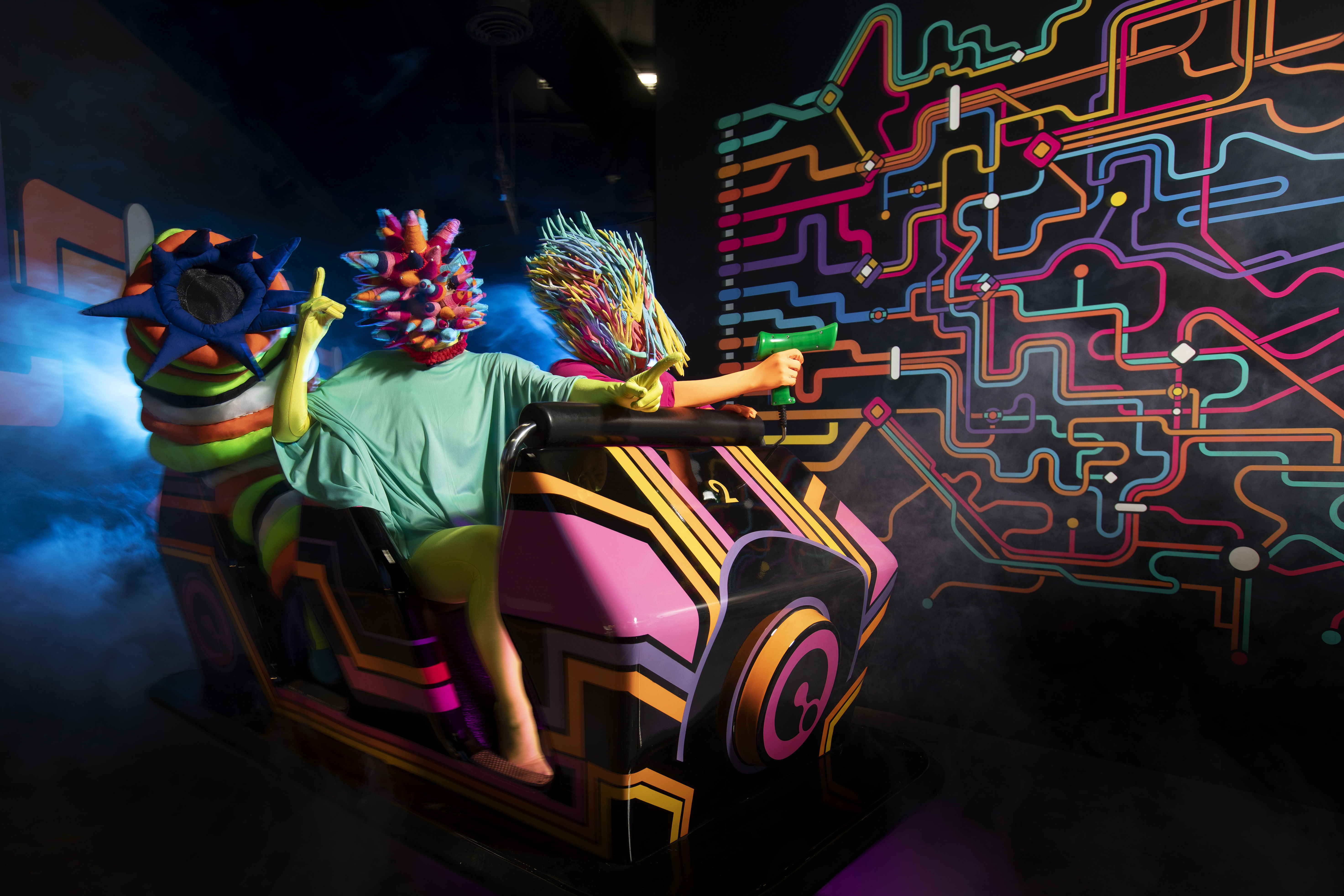 People wearing abstract masks on a rollercoaster with laser guns