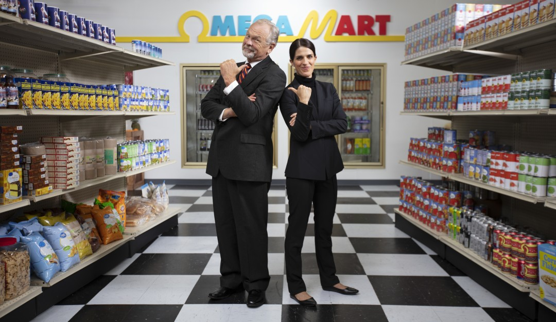 Dramcorp employees standing back to back pointing at each other inside Omega Mart