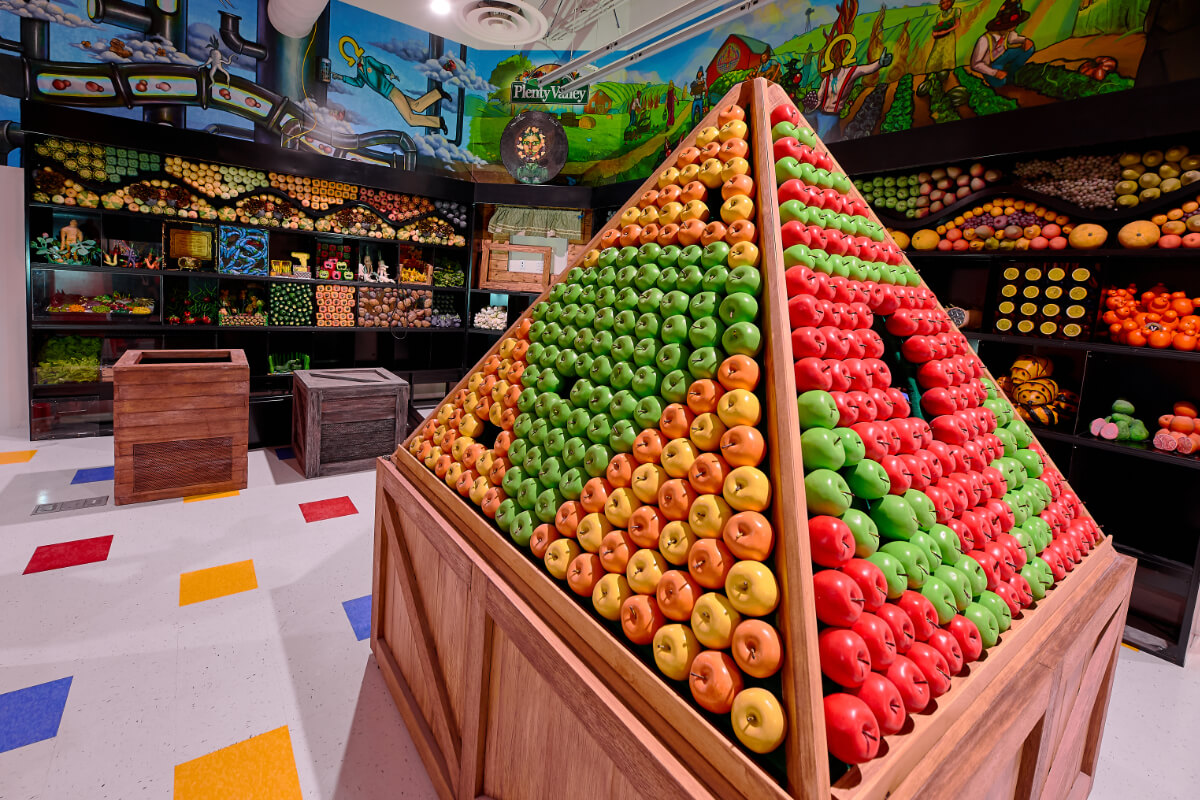 Apples stacked in a pyramid inside Omega Mart