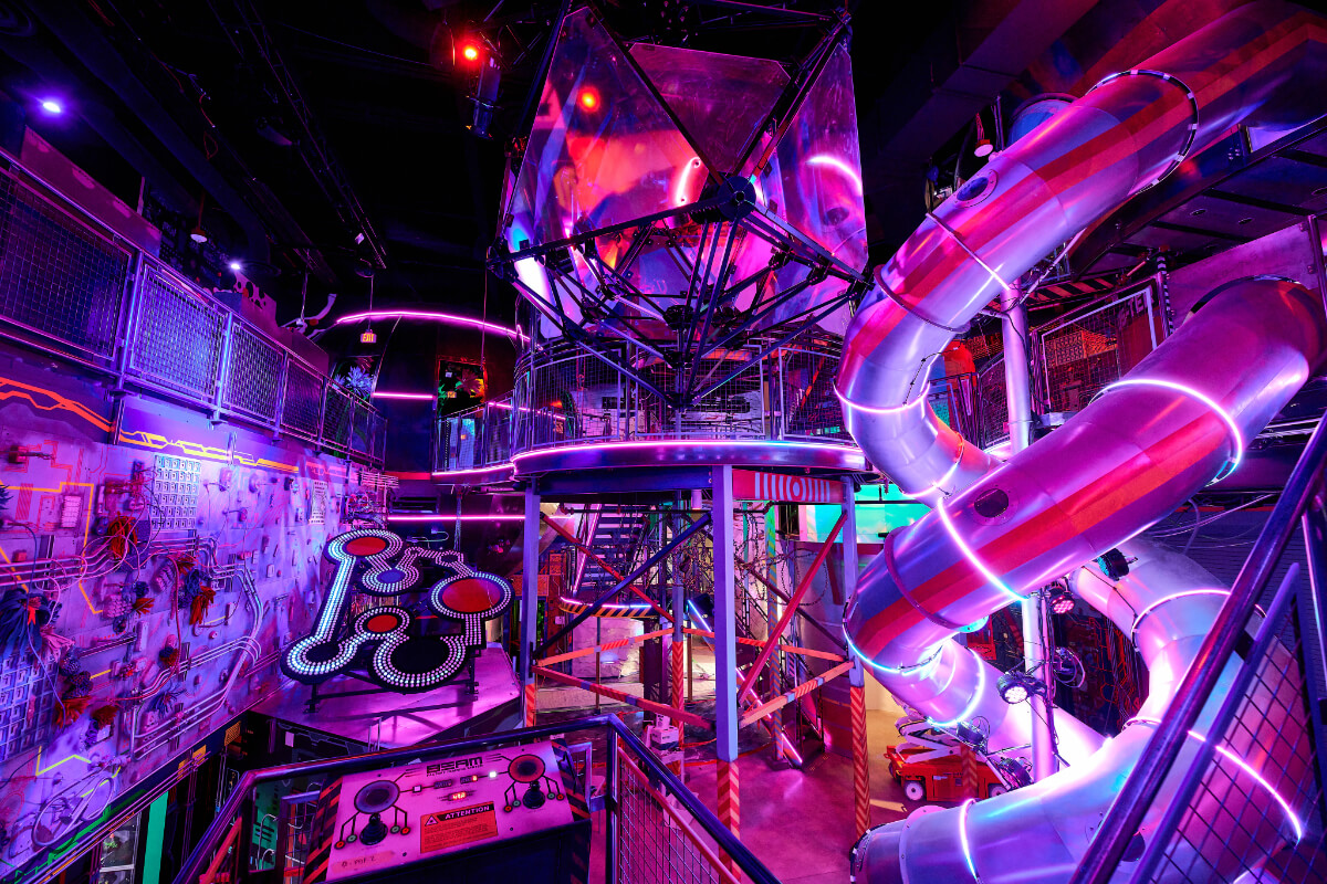 Giant slide with pink lighting at Meow Wolf Las Vegas