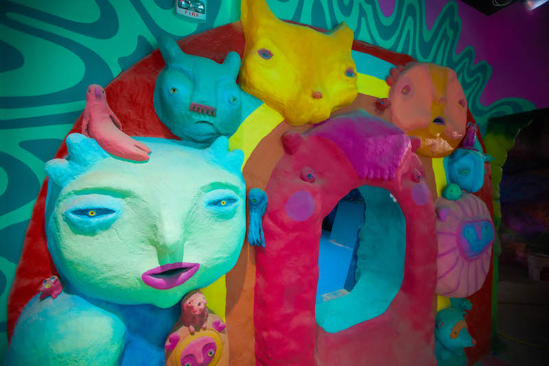Clay faces on a wall with an opening to another room inside Meow Wolf Denver