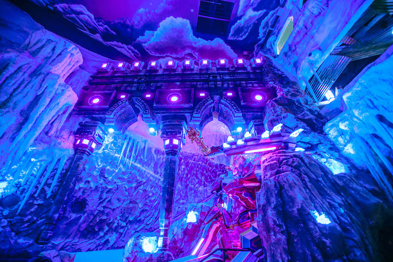 Inside Ice Castle at Meow Wolf Denver with a purple glow and icicles hanging all around