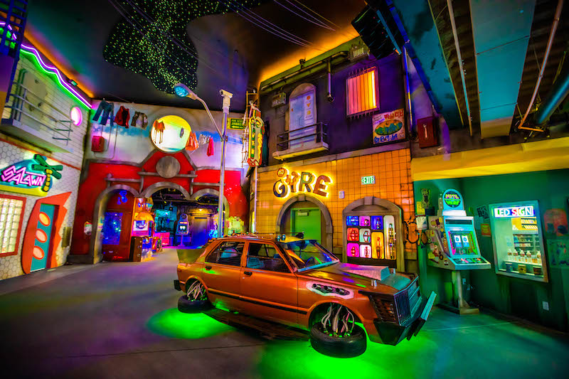 Floating orange older model car with green lights underneath and shops surrounding the car