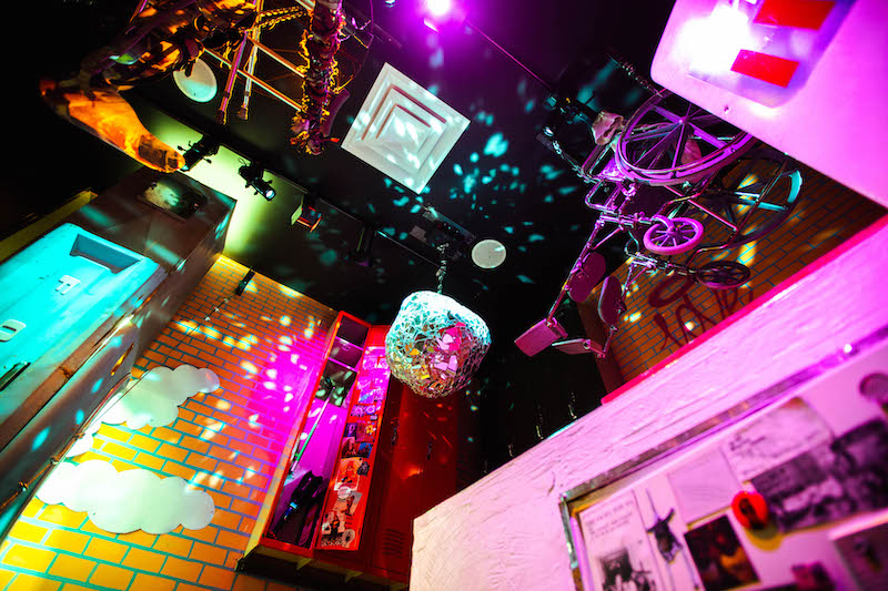 Exhibition of abstract art hanging from ceiling including a misshaped disco ball and a purple wheelchair