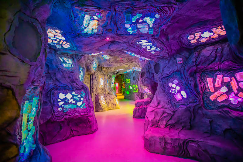 Alien looking interior. Purple cave with glowing elements imbedded in the walls and ceiling
