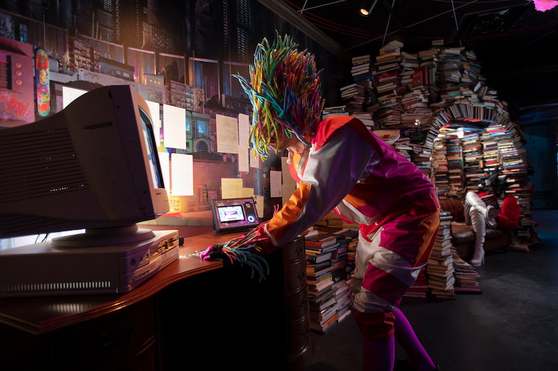 Person with head covering that looks like a creature from the multiverse leaning over a computer monitor inside Meow Wolf Denver's Convergence Station.