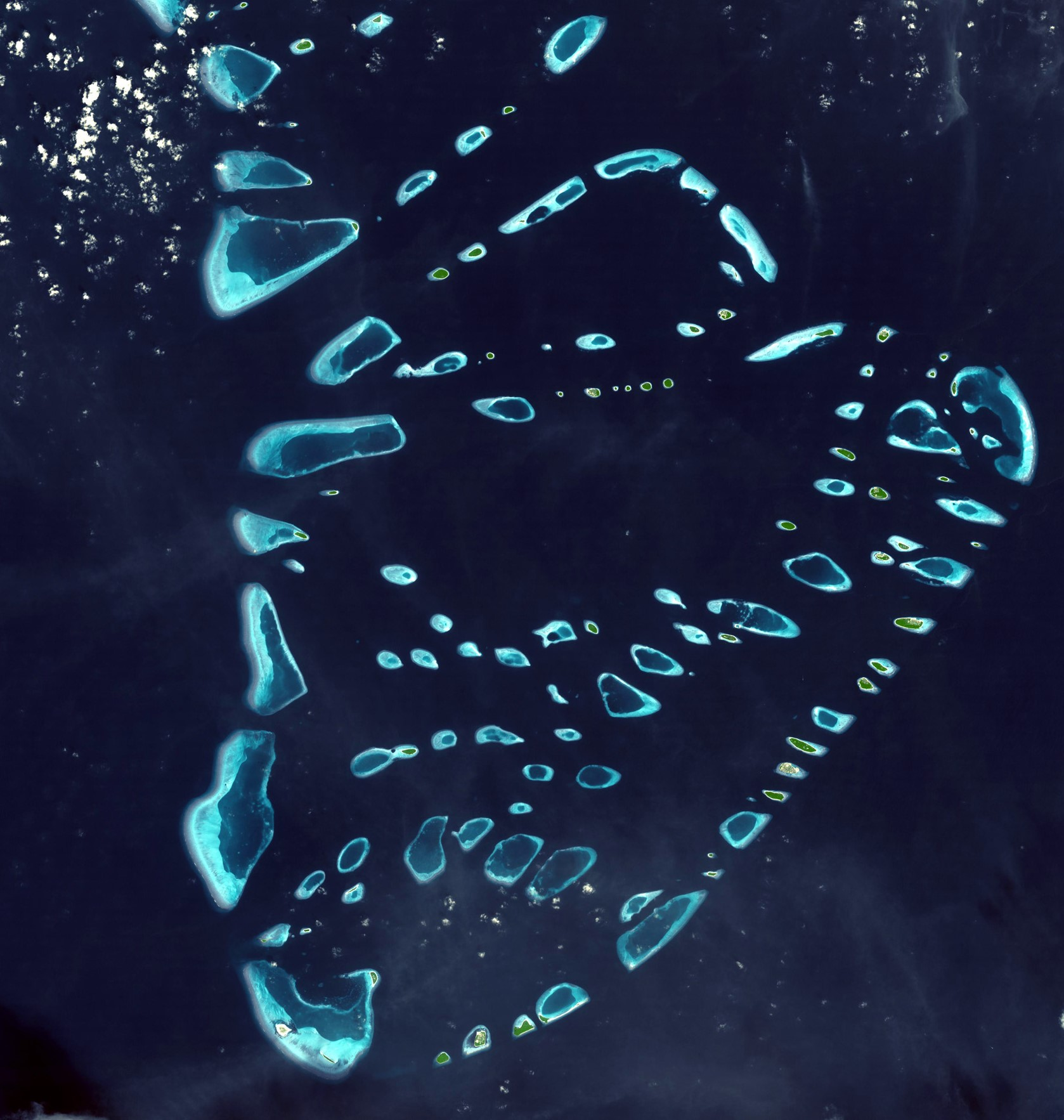 Image 3 Satellite view of Baa Atoll - Maldives, showing turquoise island reef lagoons nested within the dark blue waters of the intra-atoll lagoon and its channels. Image credit: NASA/GSFC/METI/ERSDAC/JAROS, and U.S./Japan
