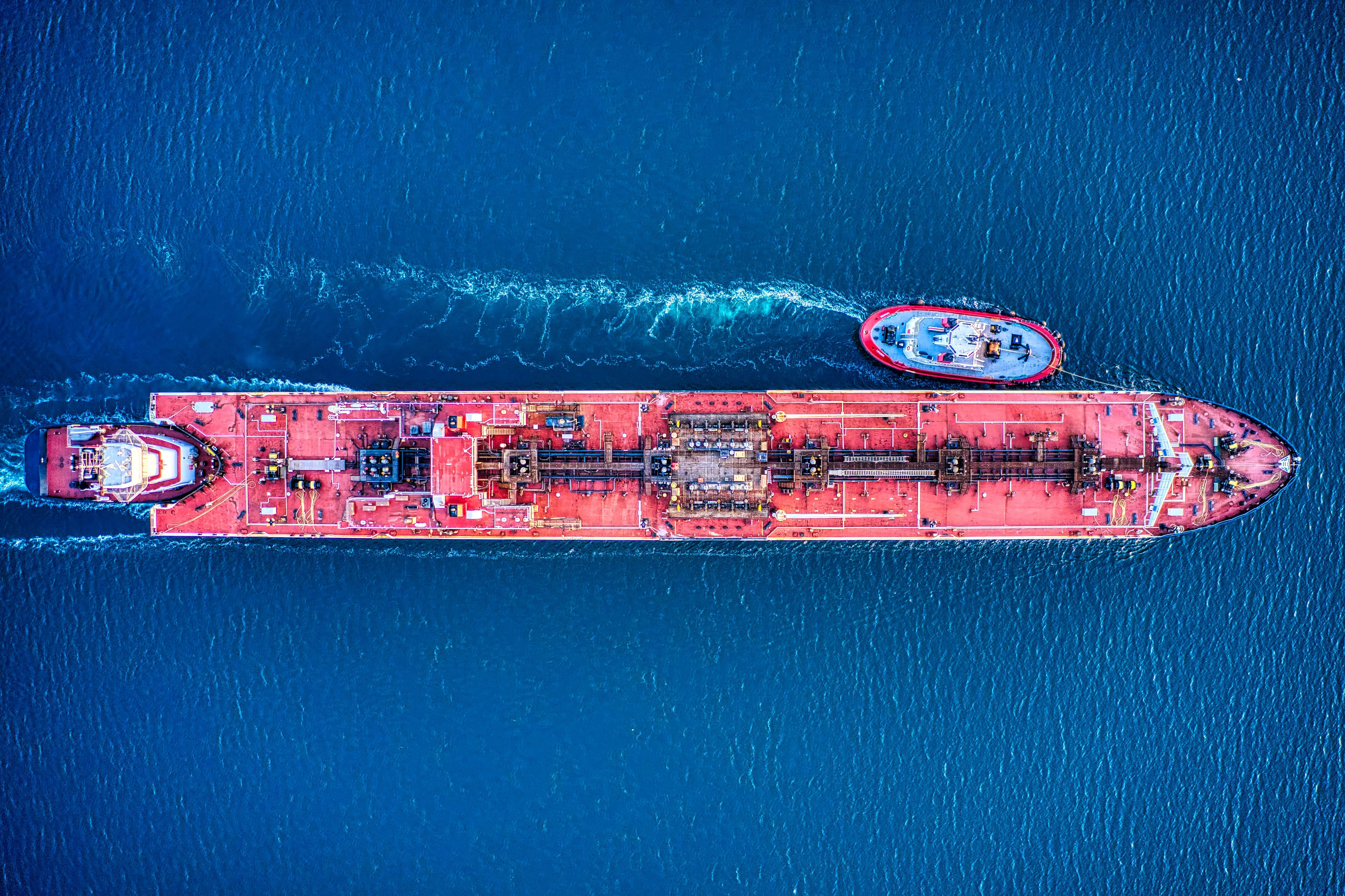 Red tanker and tug boats in ocean.