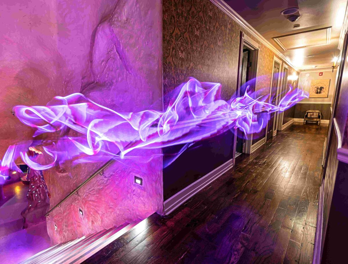 A mysterious purple wave travels down a house hallway at the House of Eternal Return