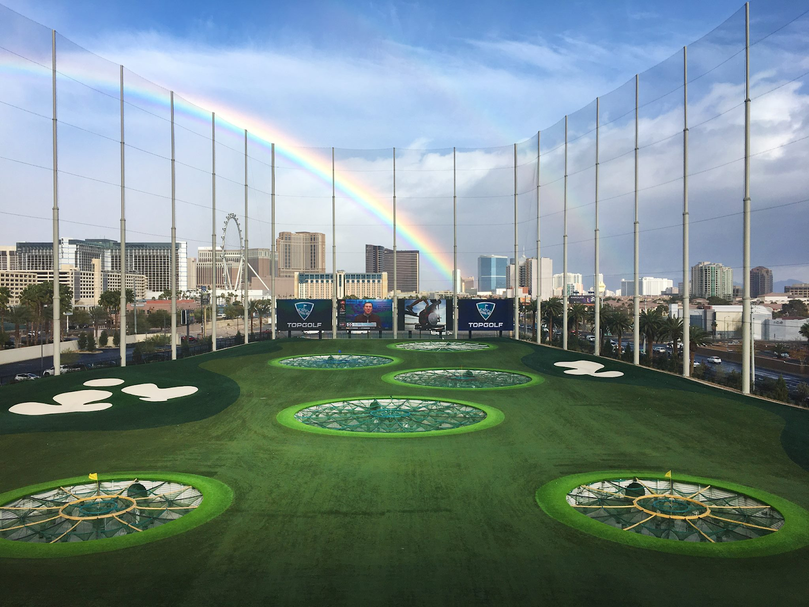 Top Golf with rainbow in the background in the sky