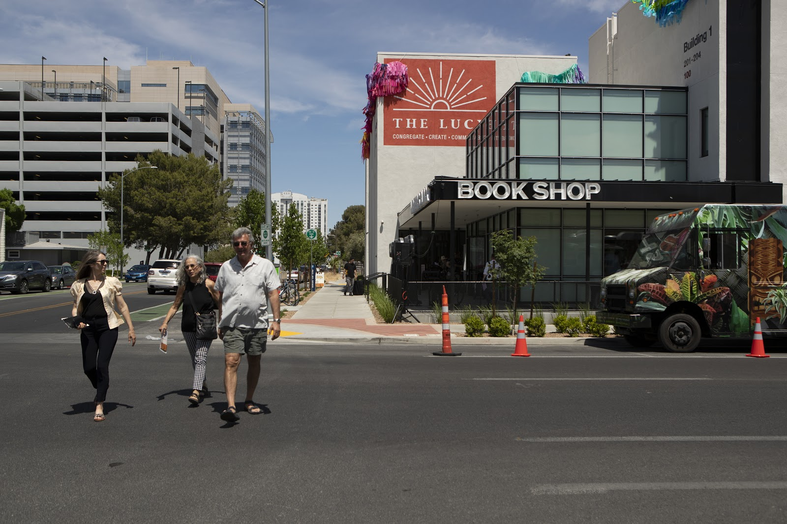 people walking down the street past a store named Book Shop