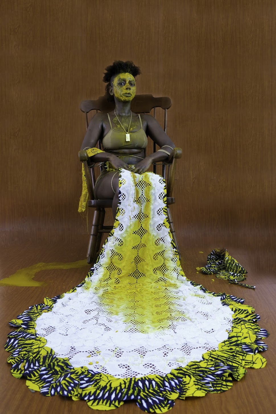Woman with yellow paint on her face sitting in a chair with a piece of fabric with yellow paint