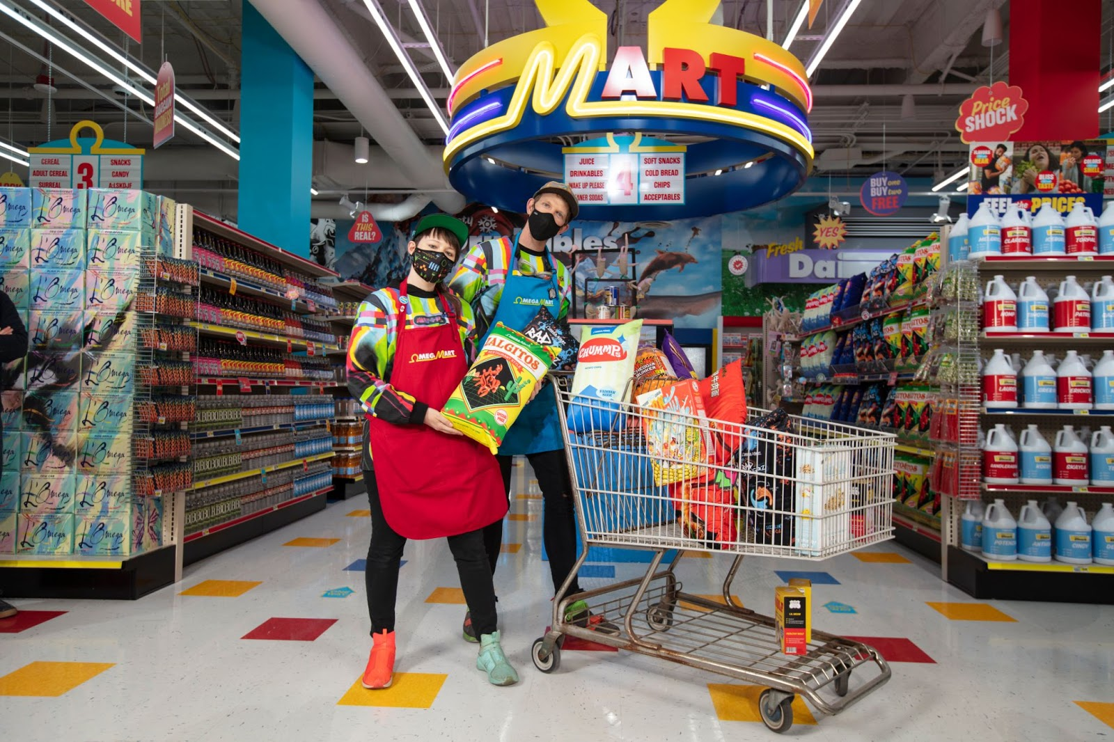 Meow Wolf Co-founders, Emily Montoya and Benji Geary, hold Omega Mart Products in front of a shopping cart at Grand Opening