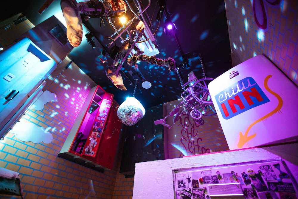 Wheelchair parts and feet on the ceiling with a disco ball