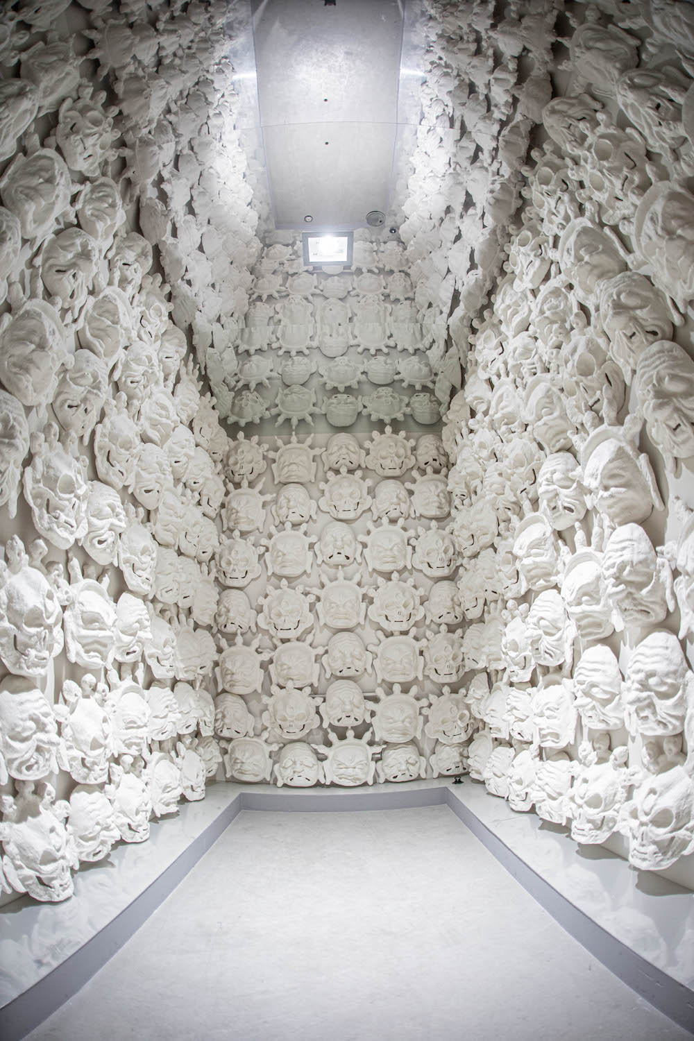 Room full of white faces made out of clay