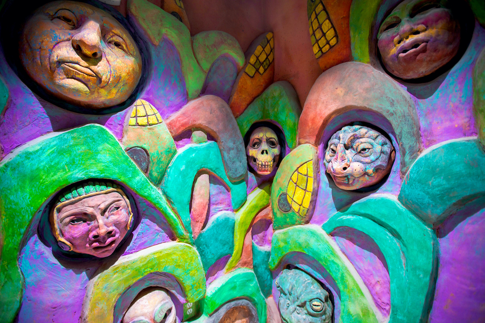 Multi-colored faces coming out of the wall
