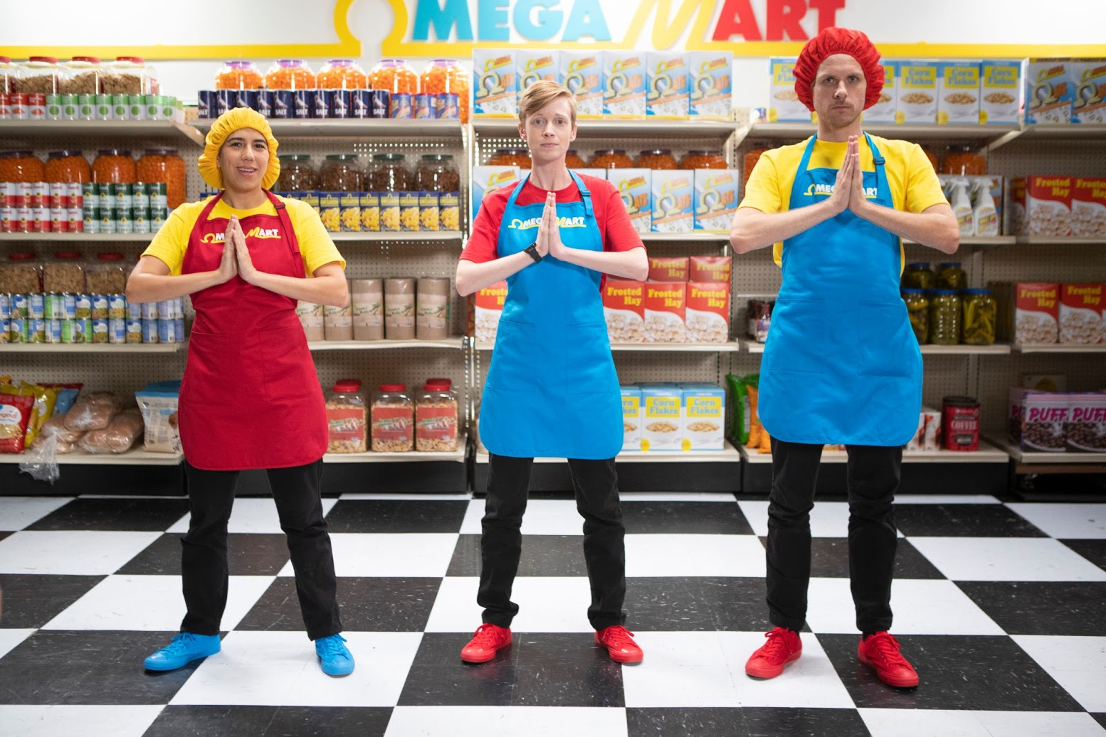 Three Omega Mart employees standing with hands in a prayer position and facing the camera
