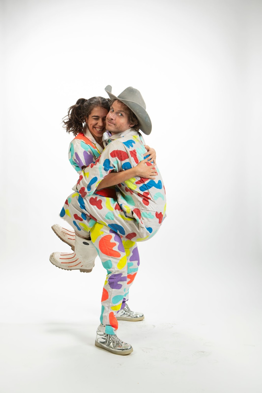 Man with legs wrapped around woman and looking at the camera. Both dressed in polka dot outfits