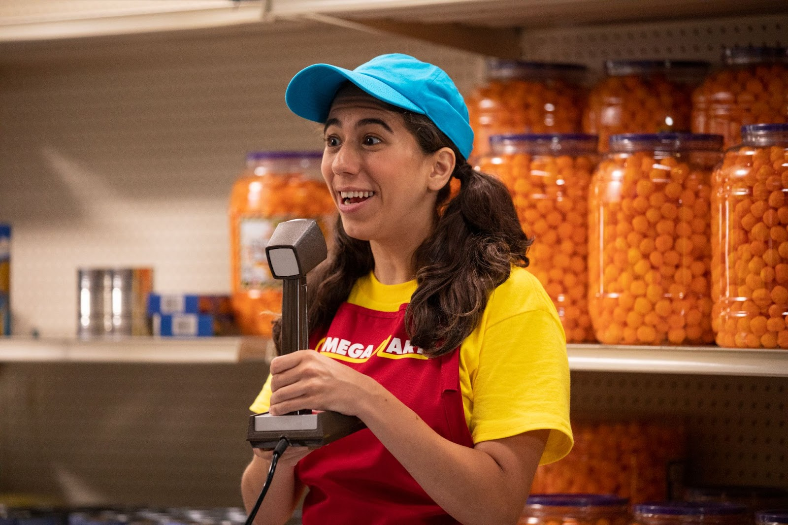 Woman with blue hat and pigtails holding a microphone inside Omega Mart