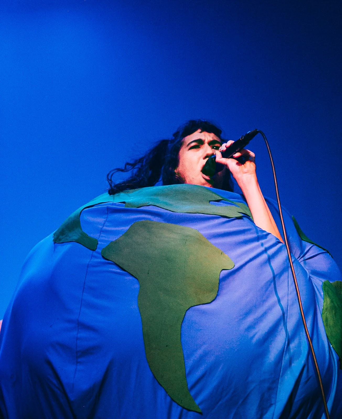 Woman dressed as the earth singing into a microphone